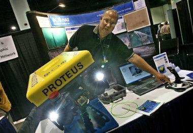 James Rall, of Hydroacustics Inc., of New York, explains uses for the Proteus ROV roaming ocean vehicle, used for exploration with cameras and lights. The ROV is controlled by a joystick. Photo credit: The Providence Journal / Steve Szydlowski